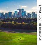 Small photo of Toronto skyline/downtown cityscape and young couple playing with dog in park below. Summer/autumn afternoon day. Toronto, Ontario, Canada