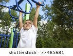 Boy playing on monkey bars - stock photo