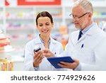 Small photo of medicine, healthcare and technology concept - apothecaries with tablet pc computer and medication at pharmacy