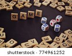 Small photo of Word GAME with wooden letters on black Board with dice and letter in the circle.