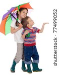 Two little children holding colored umbrella and looking up - stock photo