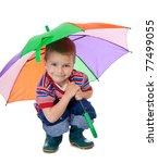 Little boy sitting under colored umbrella - stock photo