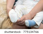 mom puts on socks baby | Shutterstock . vector #775134766