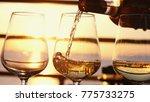 pouring white wine in glasses... | Shutterstock . vector #775733275