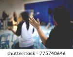 hands raised  praying worship... | Shutterstock . vector #775740646