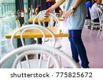 waiter organizing chairs in... | Shutterstock . vector #775825672
