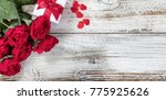 Stock photo gift box with red roses and hearts on rustic wood in flat lay view 775925626