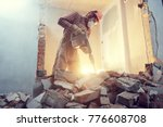Small photo of builder with hammer breaking wall indoors