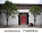 Small photo of Picture from a Tibetan monastery, a women rest below a small tree after feel sick & dizzy. the high altitude sickness is leathery & frequently happen to the tourist go Tibet, China.