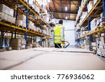 male warehouse worker pulling a ... | Shutterstock . vector #776936062