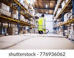 male warehouse worker pulling a ... | Shutterstock . vector #776936062