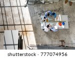 Stock photo four engineers in team making a discussion at construction site with several color helmets taken 777074956