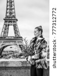 Small photo of The Party Season in Paris. trendy fashion-monger with Christmas tree in fur coat against Eiffel tower in Paris, France