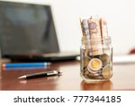 coins and banknotes in jar ... | Shutterstock . vector #777344185