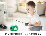 a boy playing with a car remote | Shutterstock . vector #777508612