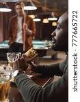 african amercian man eating...   Shutterstock . vector #777665722