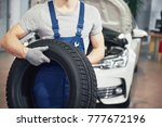 mechanic holding a tire tire at ... | Shutterstock . vector #777672196