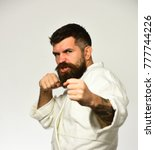 Small photo of Karate man in kimono hits hand isolated on white background. Athletic kung fu master with beard and raging face practises attack and defence. Martial arts concept