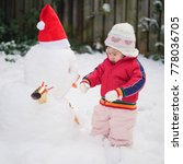 baby girl play with snowman  | Shutterstock . vector #778036705