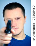 Young man taking aim with pistol - stock photo