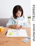 Small photo of A woman looking at the household account book