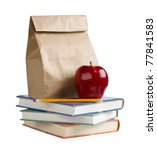 Lunch bag with apple and pencil on top of books. - stock photo