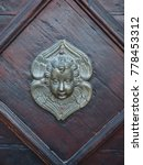 Small photo of Italian church door, detail. Golden detail in the shape of an angel's face.