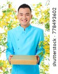 Small photo of Portrait shot of cheerful Asian man wearing traditional costume looking at camera with wide smile while holding gift box in hands, blooming ochna trees on background
