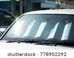 Small photo of sun shade or sun reflector on the windshield the car Protection of the car in a parking. have the light from the sun shines to the windshield