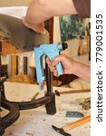 Small photo of Upholsterer repairing an antique chair using a stapler