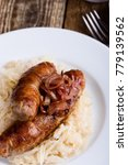 Small photo of Sausages and sauerkraut with caramelize onions on top, hearty and warming winter dish on rustic wooden table