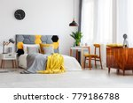 Stock photo wooden cupboard with clock next to chair at desk in cozy bedroom interior with bed against the wall 779186788