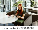 The sexy red-haired girl in a green dress sits in cafe and uses the tablet. Nearby on a table the smartphone and glasses lies.
