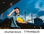 Small photo of Asian Engineer, field engineer, foreman pose in front of sidework after construction site project complete on time. Business teamwork success concept on city background