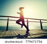 sporty female runner running on ... | Shutterstock . vector #779671756