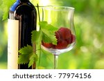 Red wine and red fruits on green background. - stock photo