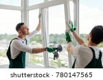 Small photo of Workers installing a window. Two guys with uplifted mood are mounting a window section on hinges of the sash.
