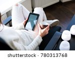 Small photo of Young woman sitting by the window with an e-book