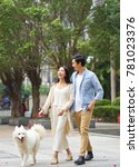 Stock photo asian couple laughing while walking dog outdoor in garden 781023376