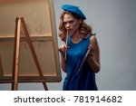 Small photo of painter draws on a gray background, draw, art, drawing, paint, easel with a canvas