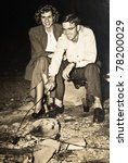 An original photograph of a couple outside cooking over an open fire. - stock photo