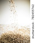 Small photo of Falling Pilsner Malt Beer Grain Heap on a White reflective Table in Studio