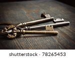 3 Antique Keys On Wooden Table