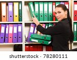 Business woman in front of shelves with folders - stock photo
