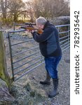 Small photo of Middle-aged man firing an air rifle on farmland on a cold, frosty day.
