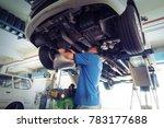 Car service, repair & maintenance. Professional car mechanic man working under lifted car in auto repair service. - stock photo