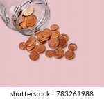 Jar Of Pennies Spilling Out On...