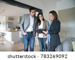 Small photo of Couple with real-estate agent visiting modern house