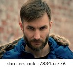 Small photo of Portrait of a bearded man in winter clothes who looks aggressively. Serious businessman. Bearded Man.
