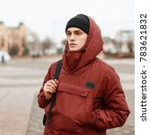 Small photo of Fashionable stylish young man in a red jacket with a hood with a black hat with a black backpack traveling on a city background